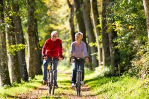 Seniorpar på sykkeltur i skogen