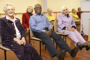 Seniorer utfører sittedans