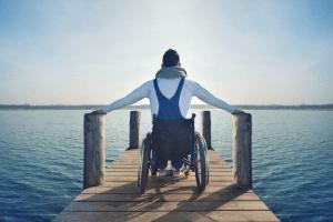 Ung mann i rullestol ser utover sjøen